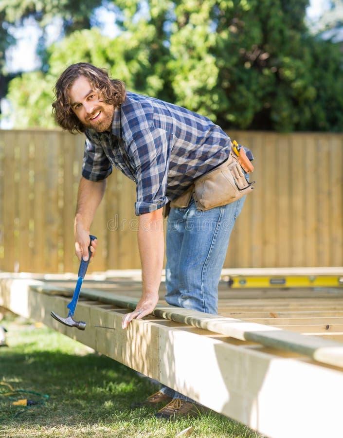 Trabalhador manual que martela o prego na madeira no local foto de stock royalty free