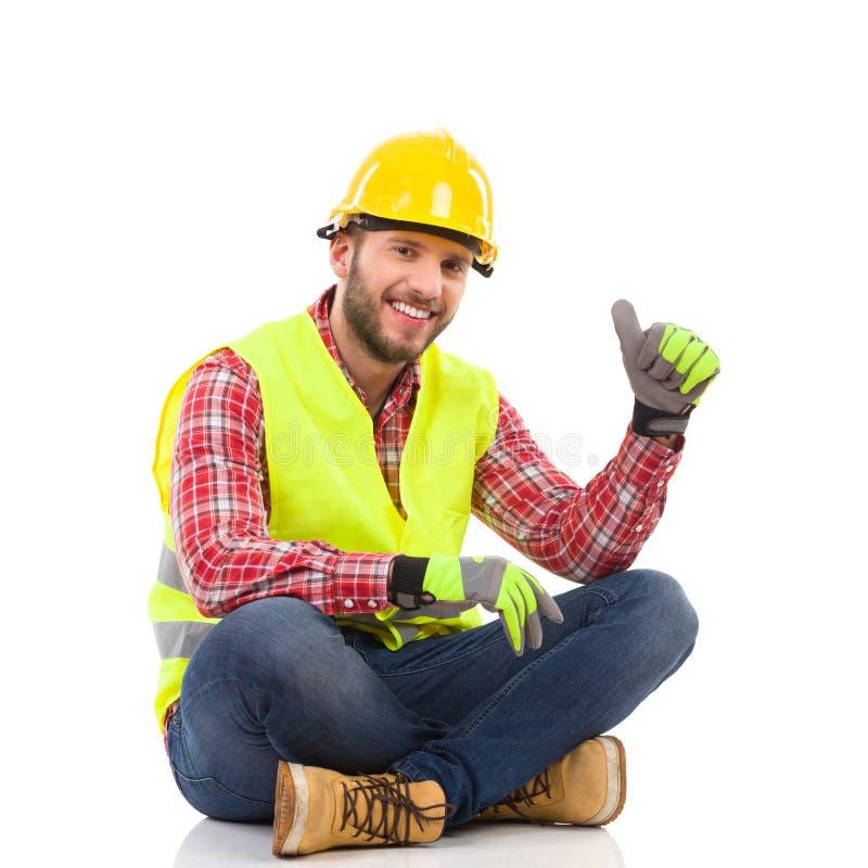 Trabalhador manual que senta-se no assoalho e que mostra o polegar acima imagem de stock