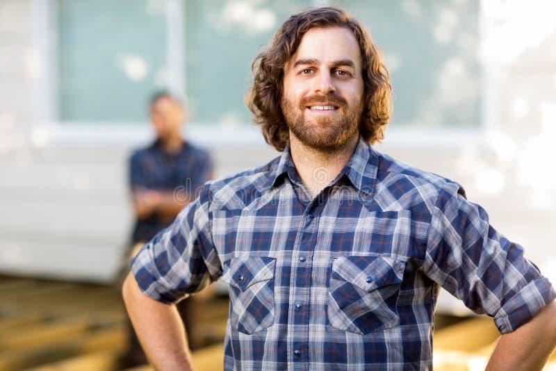 Trabalhador manual que sorri quando colega de trabalho que está dentro foto de stock