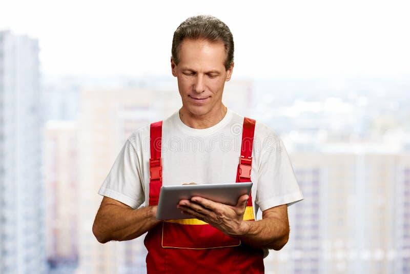 Trabalhador manual que usa a tabuleta digital imagem de stock