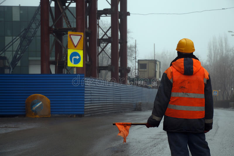Trabalhador masculino com a bandeira que está através da estrada que impede o tráfego imagem de stock