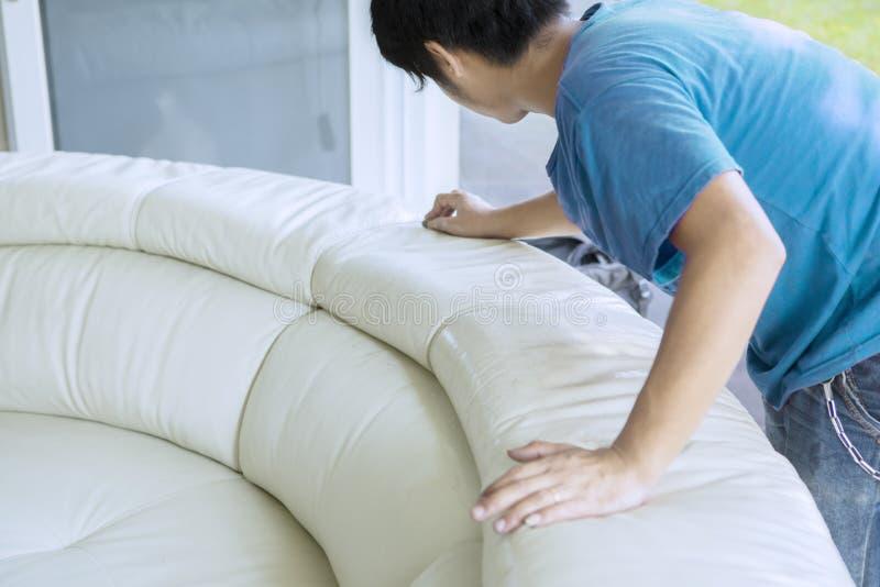 Trabalhador masculino desconhecido que limpa o sofá do couro branco imagem de stock