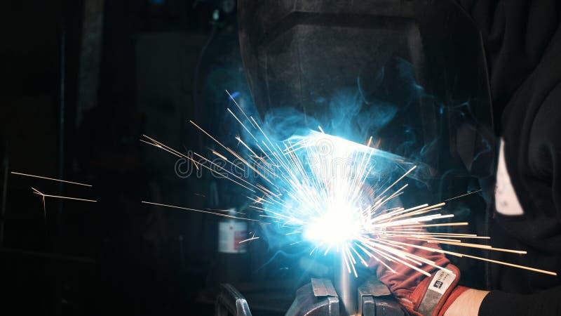 Trabalhador masculino em uma fábrica da soldadura em uma máscara da soldadura Solda em uma planta industrial foto de stock royalty free