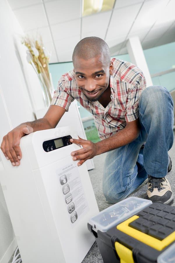 Trabalhador masculino instalando desumidificador fotografia de stock royalty free