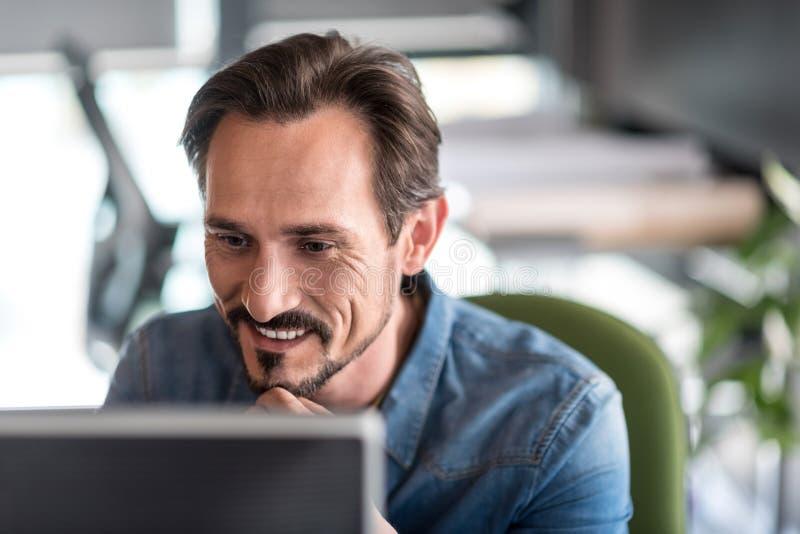 Trabalhador masculino interessado que senta-se no escritório imagem de stock royalty free
