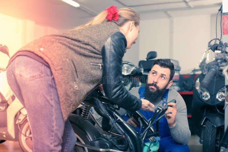 Trabalhador masculino novo que ajuda ao cliente fêmea em reparar o motorcy foto de stock