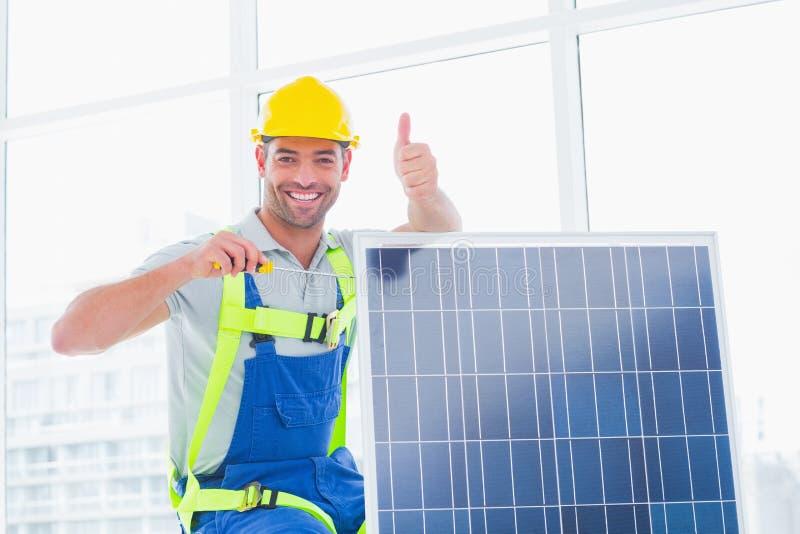 Trabalhador masculino que aperta o painel solar ao gesticular os polegares acima foto de stock royalty free