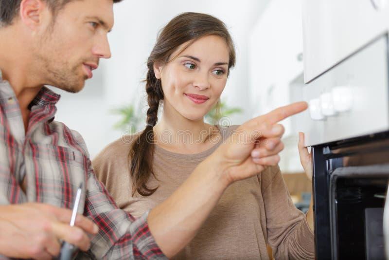 Trabalhador masculino que repara o dispositivo do forno na mulher da presença imagem de stock