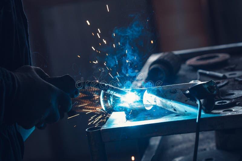 Trabalhador masculino que veste luvas protetoras ao reparar a tubulação de exaustão do carro com máquina de soldadura fotografia de stock