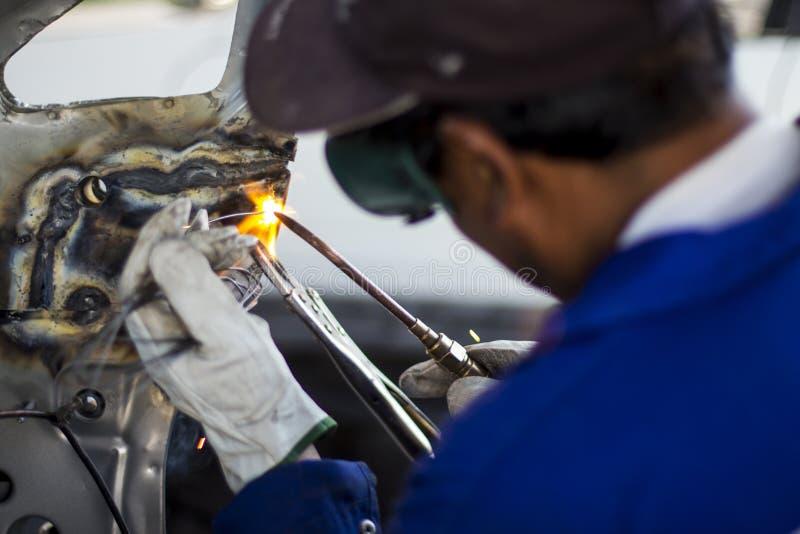 Trabalhador mecânico do homem que repara um corpo de carro em uma garagem - segurança no trabalho com desgaste da proteção Trabal imagem de stock royalty free