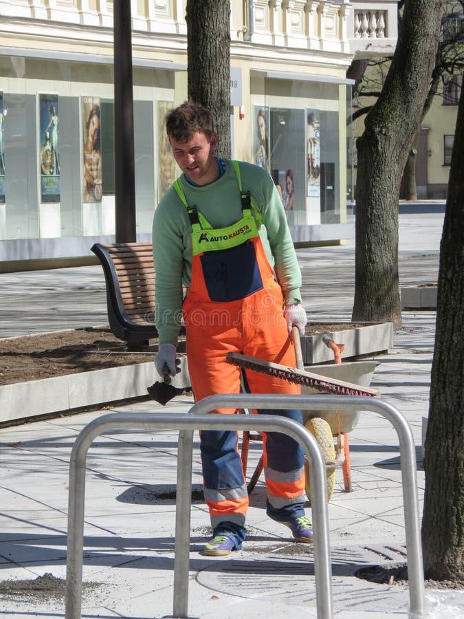 Trabalhador não identificado da estrada com um carrinho de mão de roda fotografia de stock