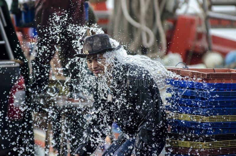 Trabalhador não identificado do barco de pesca que lava no molhe imagem de stock royalty free