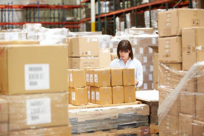 Trabalhador no armazém que prepara bens para a expedição imagens de stock royalty free