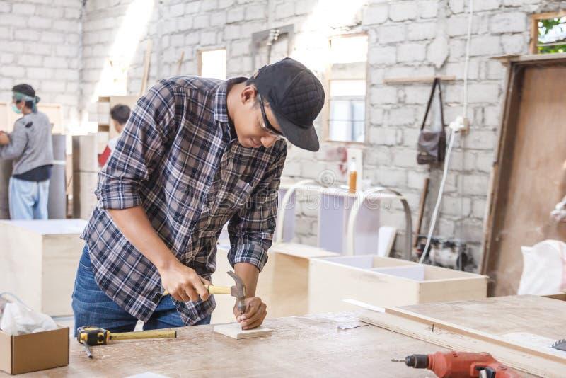 Trabalhador no espaço de trabalho do carpinteiro que instala o prego usando o martelo fotos de stock