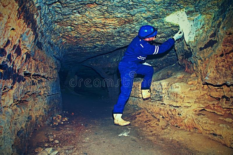 Trabalhador no túnel O pessoal em uma verificação do terno protetor sedimenta na parede rochosa imagem de stock