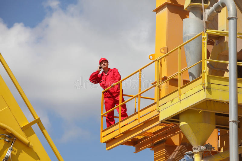 Trabalhador no telefone chamando uniforme na plataforma industrial foto de stock royalty free