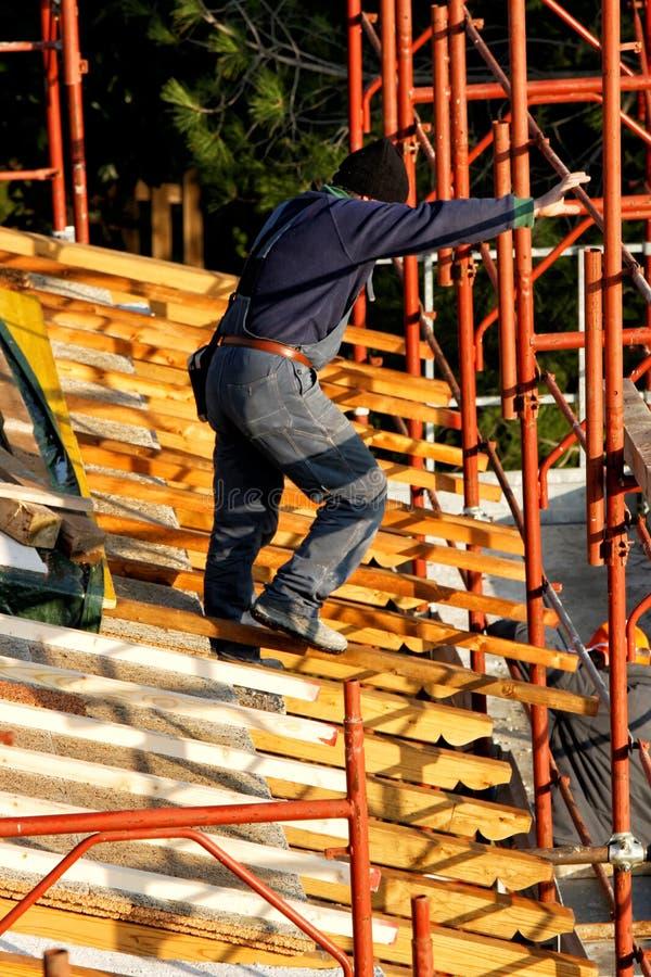 Trabalhador no telhado, casa sob a construção foto de stock