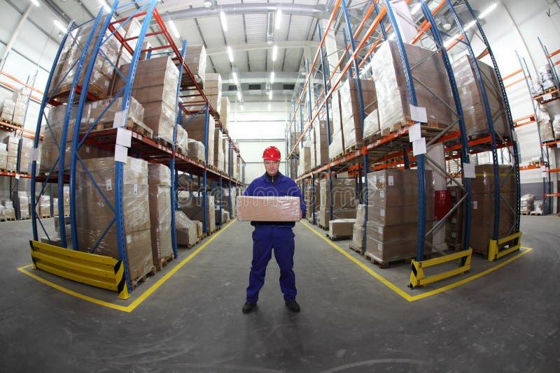 Trabalhador no uniforme com a caixa no armazém foto de stock