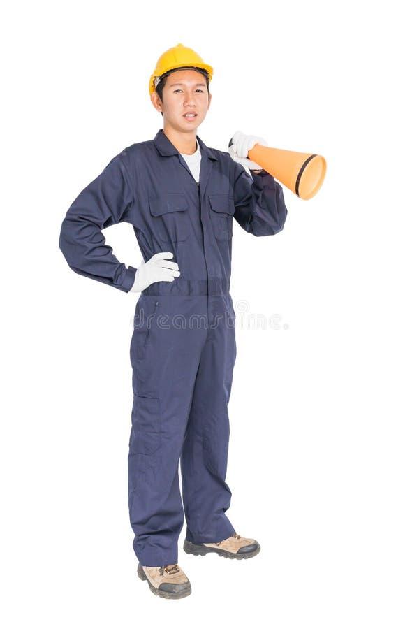 Trabalhador novo com o capacete amarelo que guarda um megafone fotografia de stock