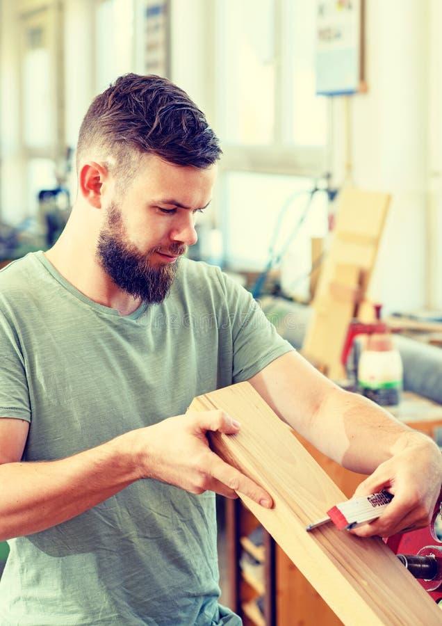 Trabalhador novo em uma oficina dos carpinteiros fotos de stock