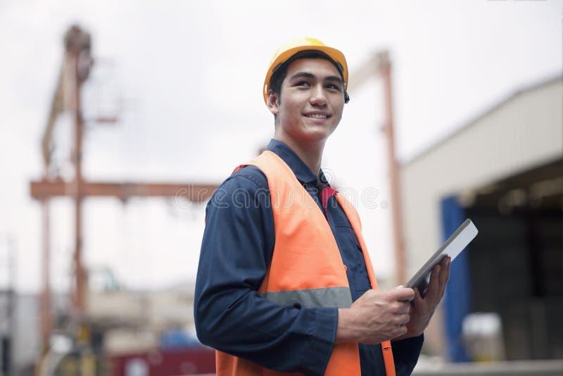 Trabalhador novo orgulhoso no desgaste protetor do trabalho em uma jarda de envio foto de stock royalty free