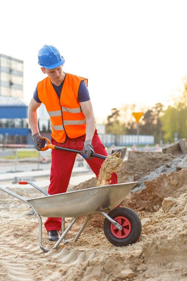 Trabalhador novo que carrega um carrinho de mão fotos de stock