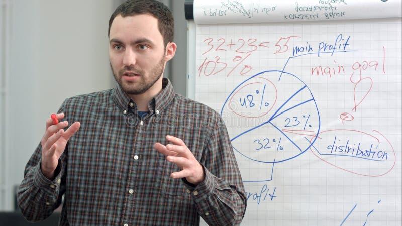 Trabalhador novo que faz a apresentação do negócio usando o flipchart imagem de stock