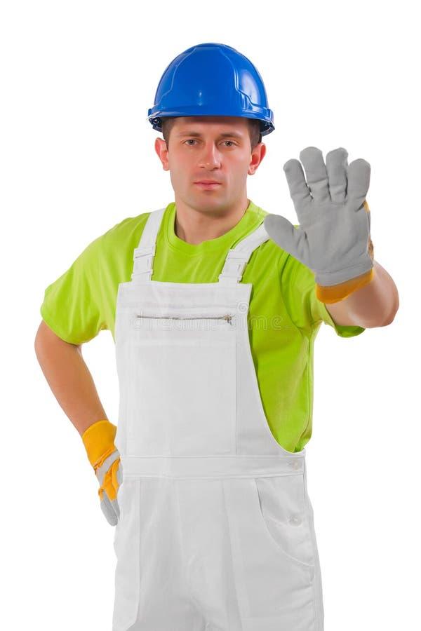 Trabalhador novo que mantém os braços no simbol da parada isolados foto de stock