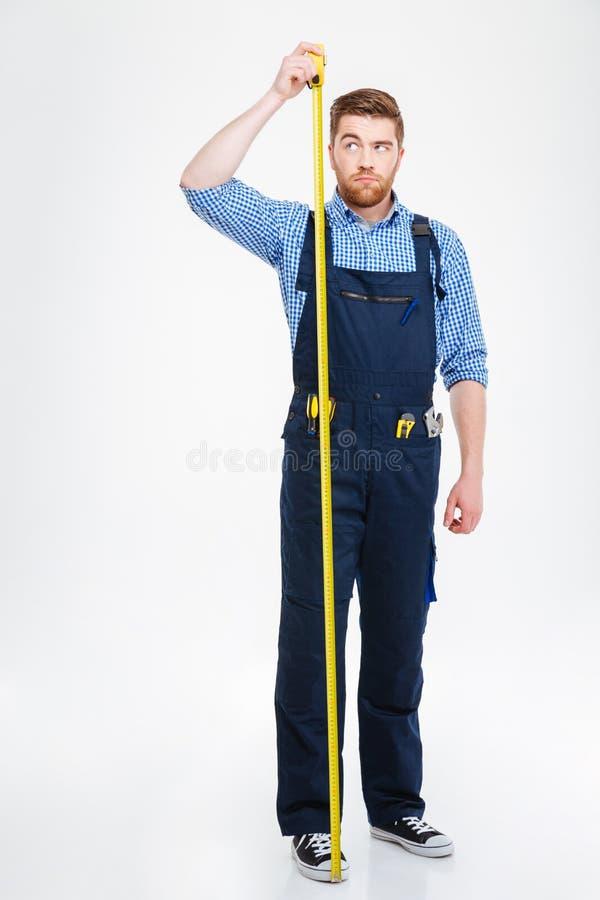 Trabalhador novo sério que está e que mede seu crescimento com fita fotos de stock