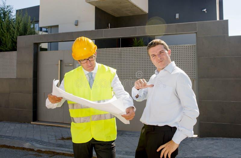 Trabalhador orgulhoso feliz do contramestre do cliente e do construtor com os modelos da construção de casa nova no conceito do n fotografia de stock royalty free