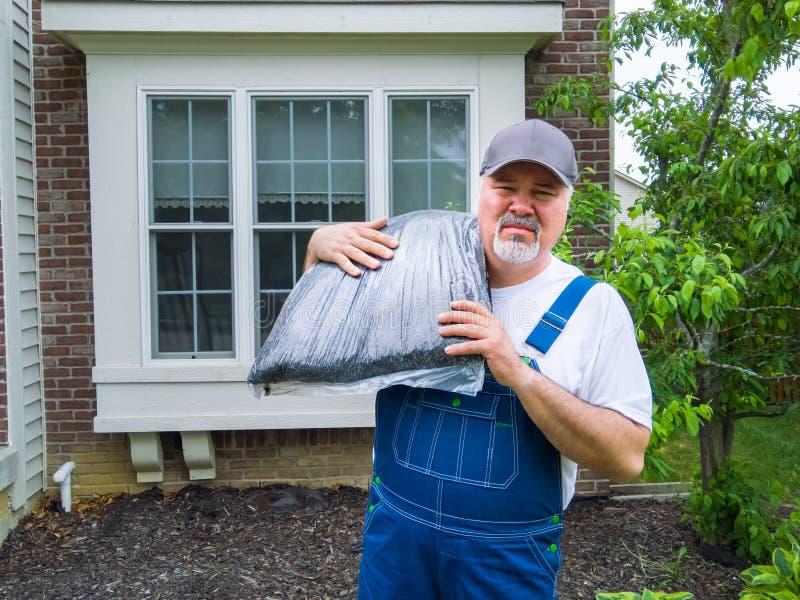 Trabalhador ou jardineiro pronto à palha de canteiro o jardim fotografia de stock