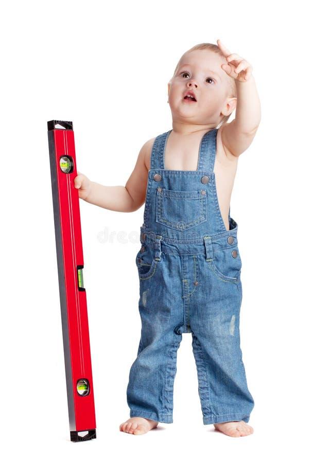 Trabalhador pequeno do bebê com nível imagens de stock royalty free