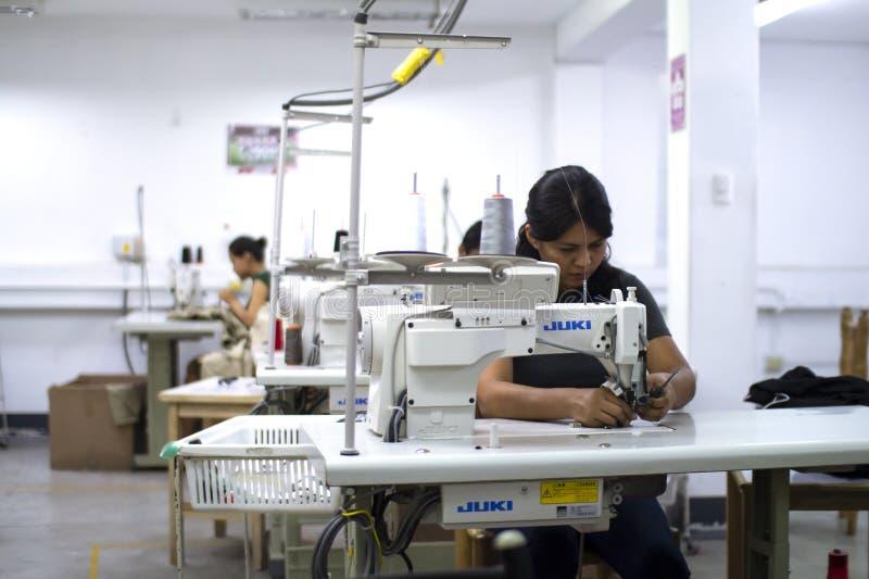 Trabalhador peruano fêmea com a máquina de costura que faz alterações à roupa imagem de stock