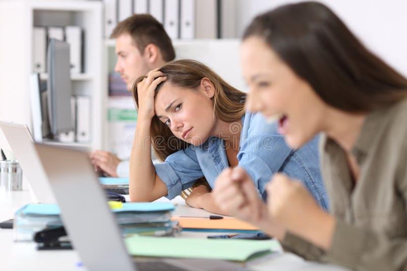 Trabalhador preocupado ao lado do bem sucedido imagem de stock royalty free