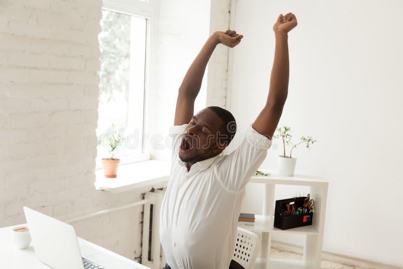 Trabalhador preto cansado que boceja e que estica na cadeira do escritório foto de stock