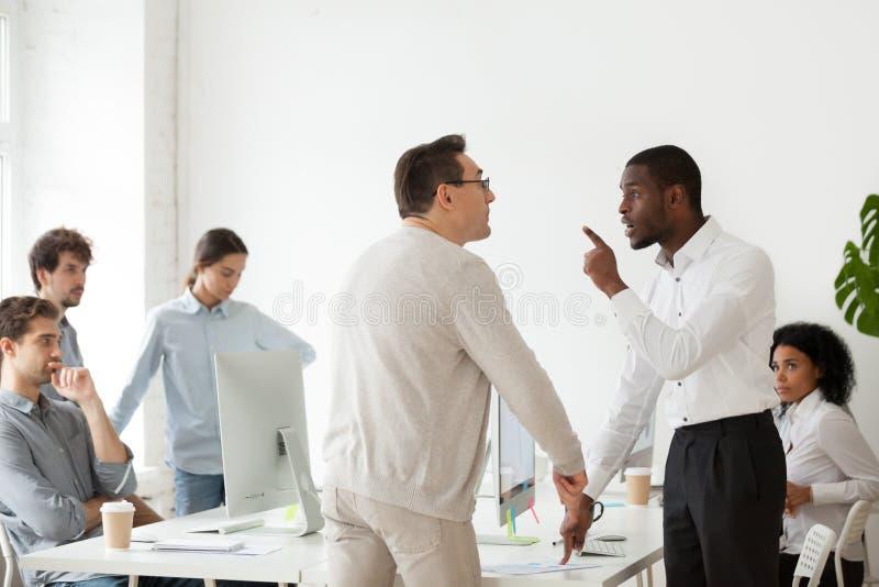 Trabalhador preto irritado que disputa com o colega caucasiano mais idoso fotos de stock royalty free