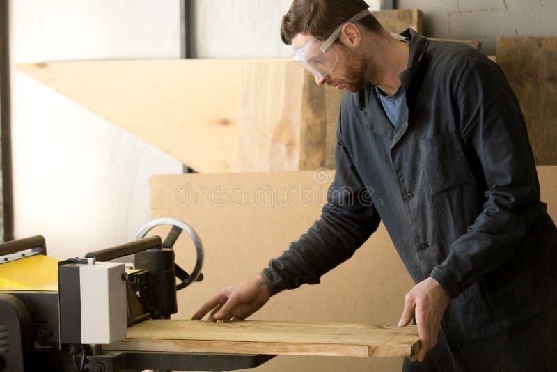 Trabalhador produzindo a madeira serrada na serração local foto de stock royalty free
