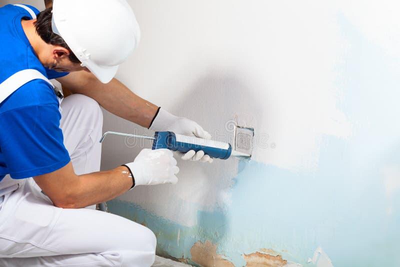Trabalhador profissional que aplica o vedador do silicone com arma de calafetagem fotos de stock