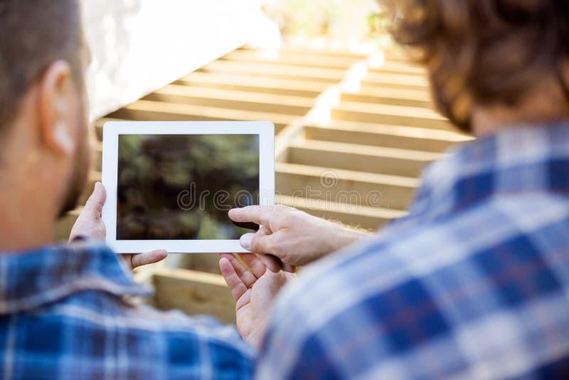 Trabalhador que aponta na tabuleta de Digitas quando colega de trabalho imagens de stock royalty free