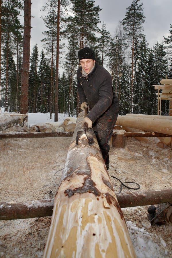 Trabalhador que barbeia a casca os logs usando a pá de desembarque fotos de stock
