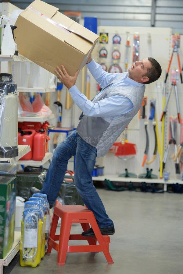Trabalhador que cai fora escada no armazém fotos de stock