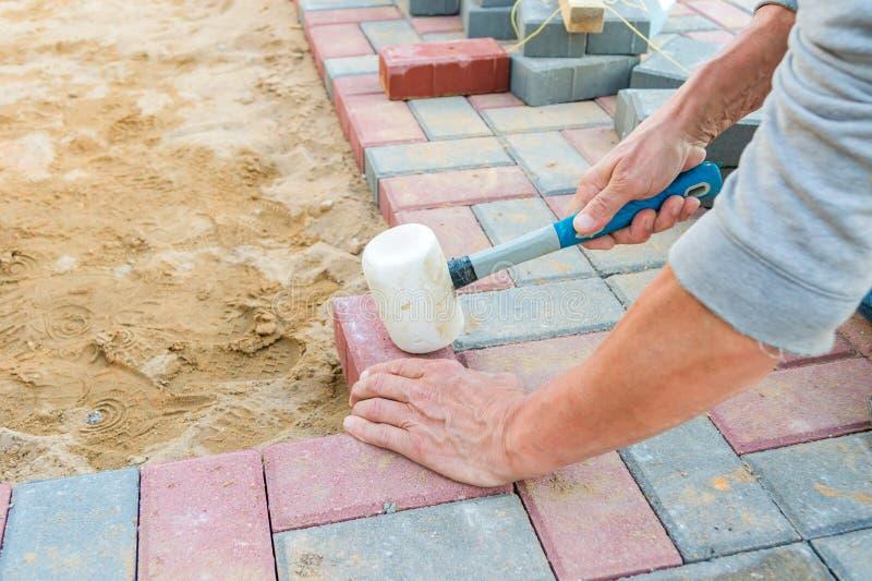 Trabalhador que coloca blocos de pavimentação concretos vermelhos e cinzentos Estrada que pavimenta, constru??o fotos de stock royalty free