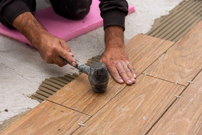 Trabalhador que coloca telhas de assoalho cerâmicas na superfície adesiva, nivelando imagens de stock royalty free