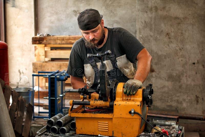 Trabalhador que corta a tubulação de aço com a máquina para rosquear foto de stock