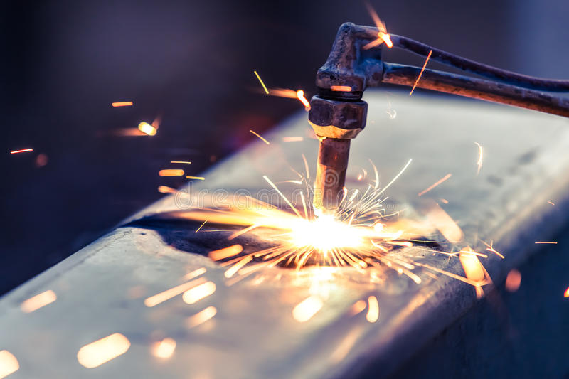 Trabalhador que corta a tubulação de aço usando a tocha do metal fotografia de stock