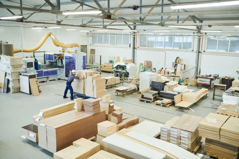 Trabalhador que empilha pranchas de madeira imagem de stock