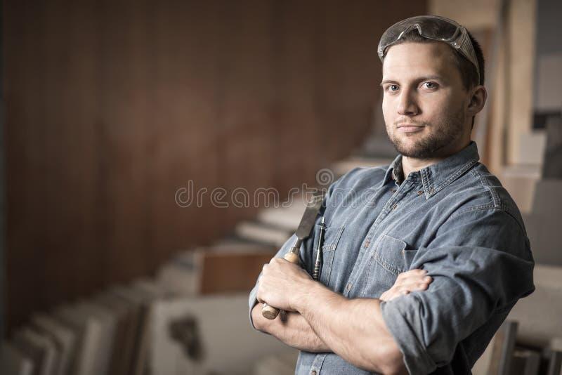 Trabalhador que está com um formão foto de stock royalty free