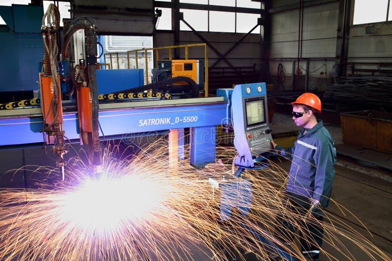 Trabalhador que está perto do cutt do metal do plasma do painel de controle da máquina foto de stock