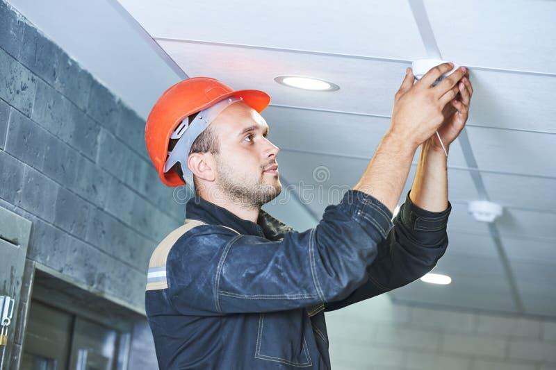Trabalhador que instala o detector de fumo no teto foto de stock