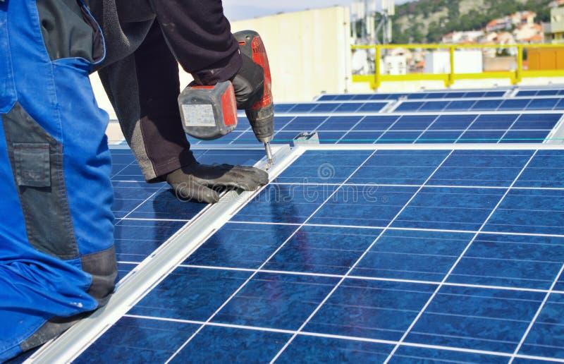 Trabalhador que instala os painéis solares fotografia de stock